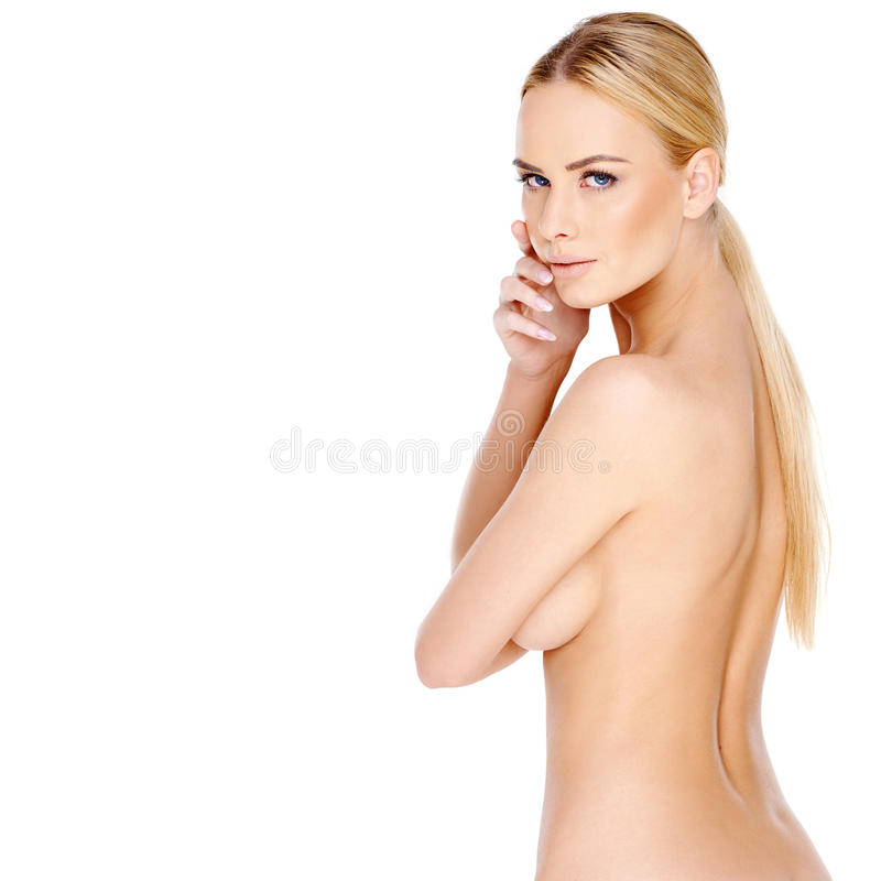 Pretty young blond woman posing topless. Turning to look back over her shoulder at the camera with a serious expression on white stock images