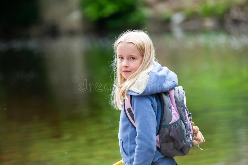 Pretty young blonde girl looking back over shoulder with backpack on. Out of focus river scene in background royalty free stock photography