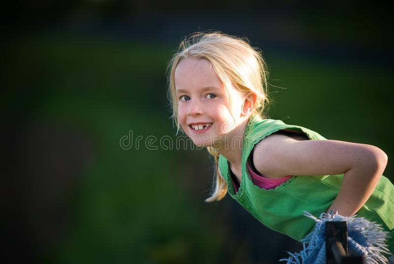 Pretty young blonde girl smiling in light from setting sun stock photography
