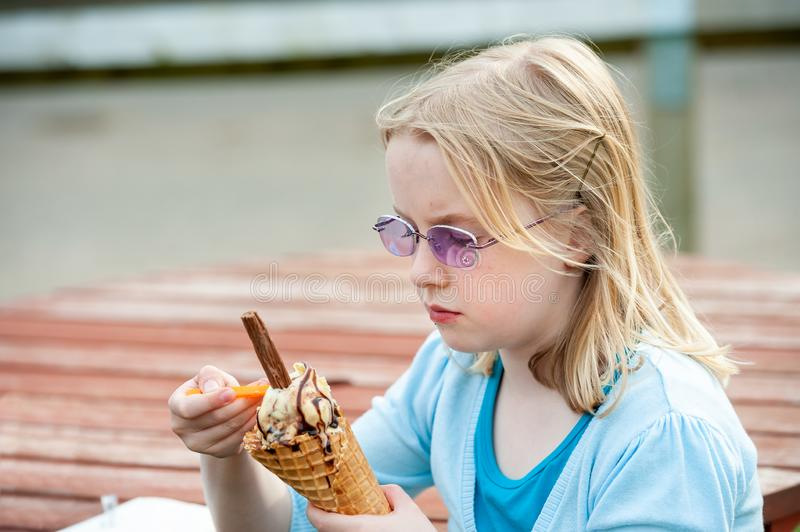Pretty young blonde girl wearing purple sunglasses and enjoying a large ice cream with chocolate flake royalty free stock photography