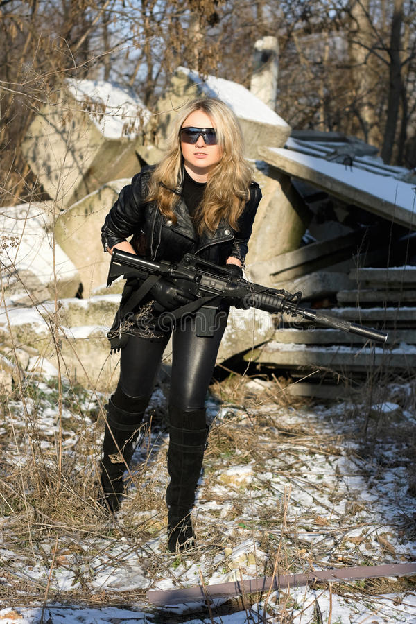 Pretty young blonde with a gun stock image