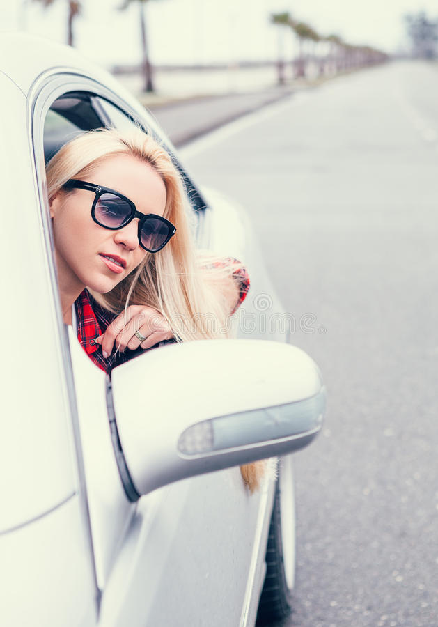 Pretty young blonde woman looks out from car window stock image