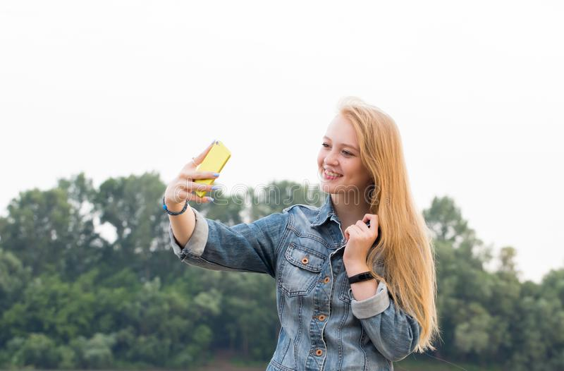 Pretty young blonde woman taking a selfie on nature background. Pretty young blonde woman smiling and taking a selfie on nature background royalty free stock images