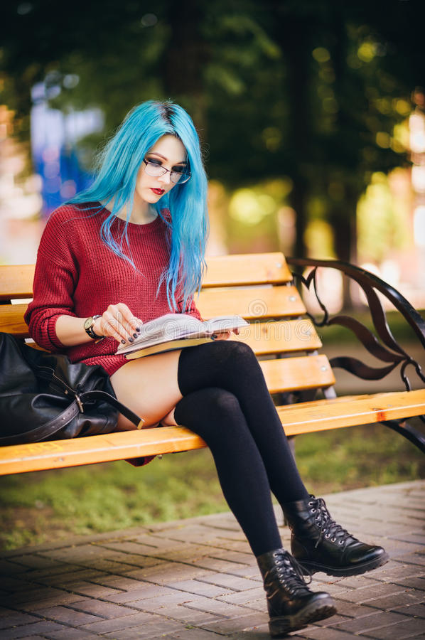 Pretty young blue-haired rock girl sitting on bench in square and reading a book stock photo