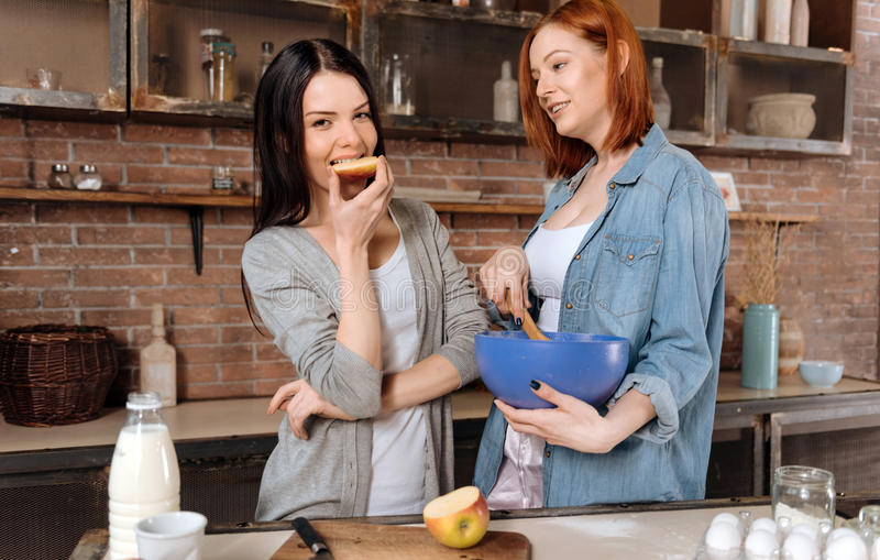 Pretty young brunette eating apple. Enjoy your meal. Delighted attractive girl holding left hand on the belly looking straight at camera while eating piece of stock photos