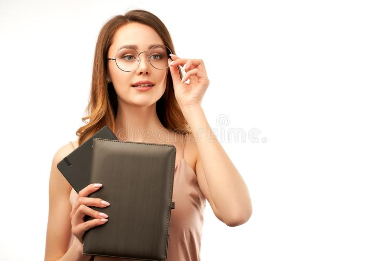 A pretty young brunette girl holds a notebook in her hands and holds her glasses with hand, trying to see the inscriptions stock image