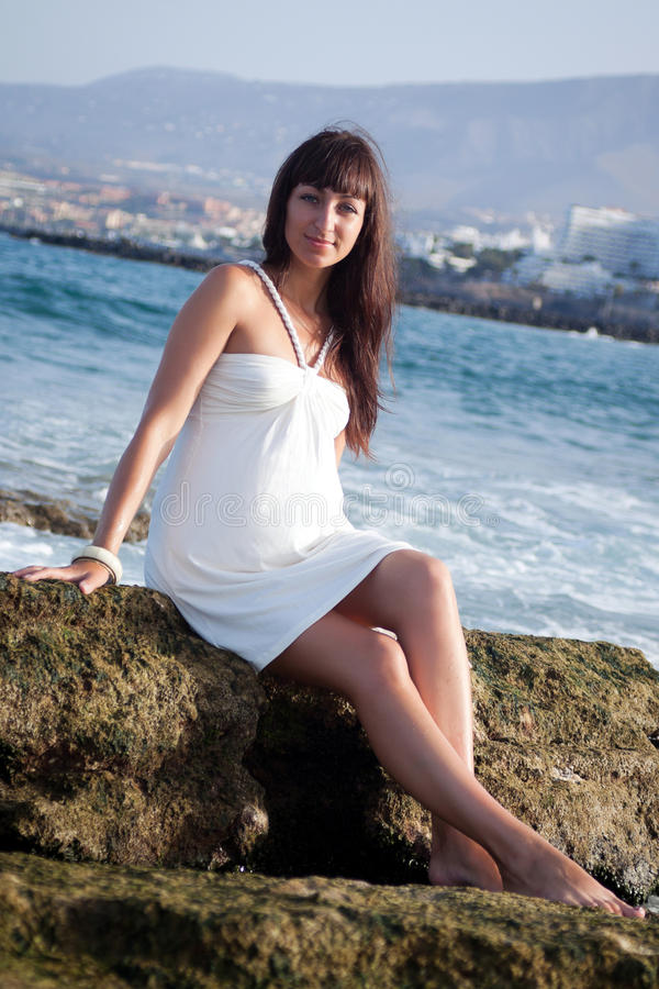 Pretty young brunette on a rocky beach stock image