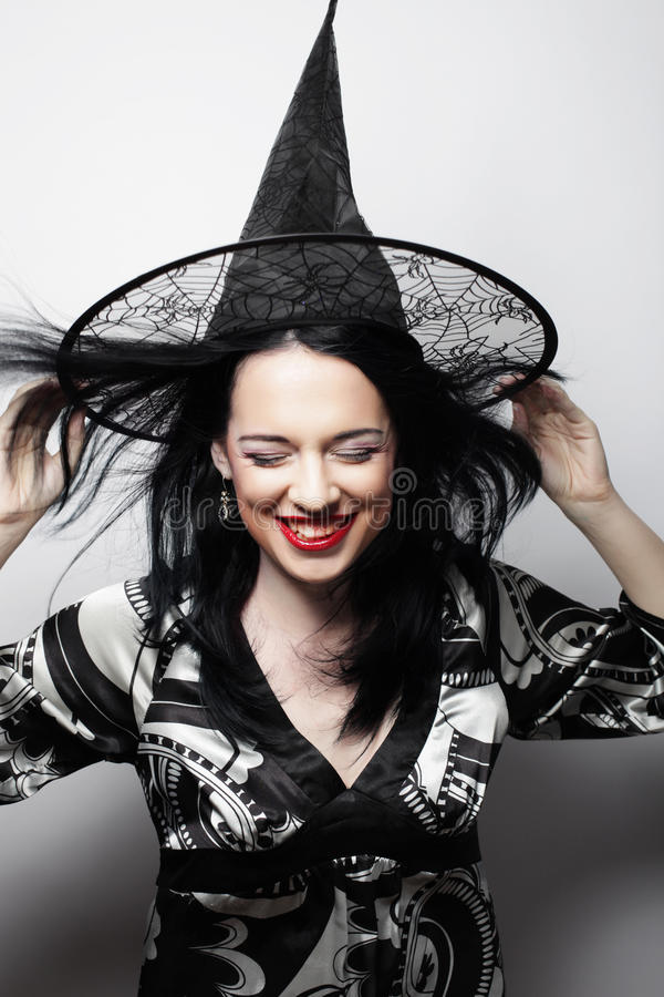 Pretty young brunette witch with black hat royalty free stock image
