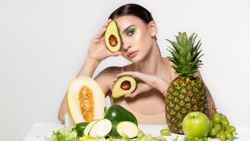 Pretty young brunette woman covering eye with fresh ripe green avocado, sits by the table with fruits and vegetabels stock photo