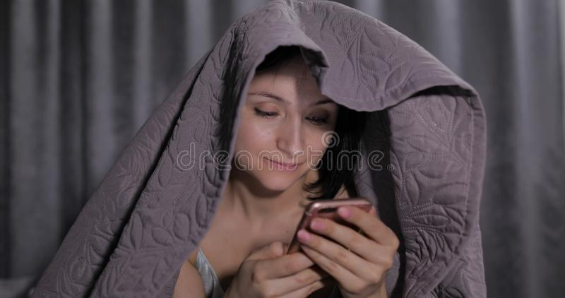 Woman sitting on bed under blanket and enjoying chatting to friend on smartphone stock images