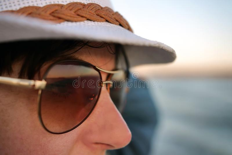 Pretty young brunette woman in sunglasses and a white hat, close-up royalty free stock photo