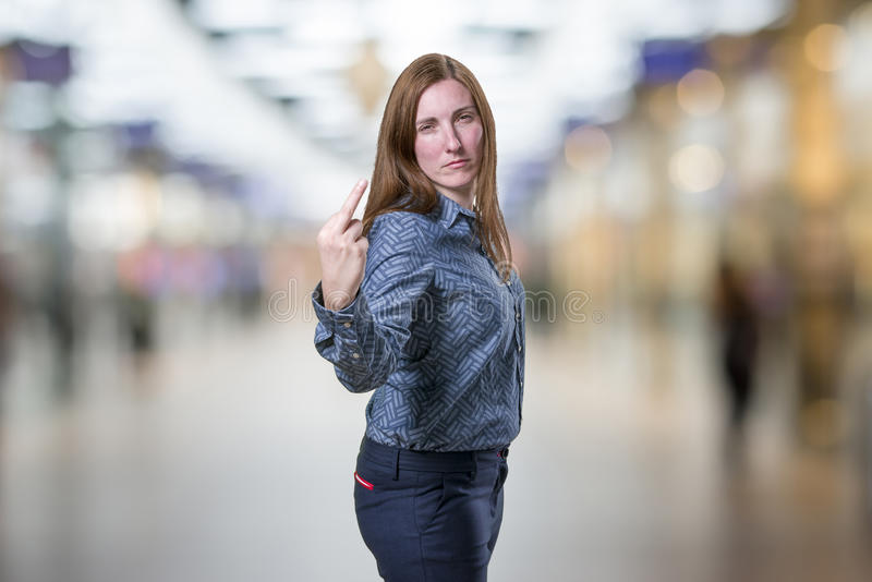 Pretty young business woman giving flipping the bird over blur b royalty free stock image