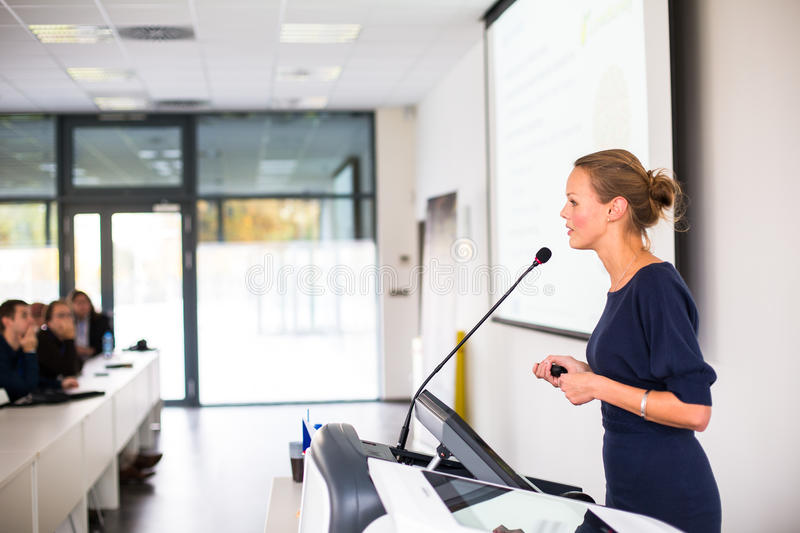 Pretty, young business woman giving a presentation stock photography