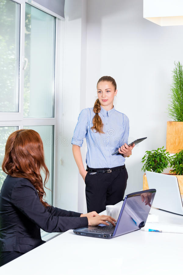 Pretty young business woman giving a presentation in conference or meeting setting. People and teamwork concept - happy royalty free stock image