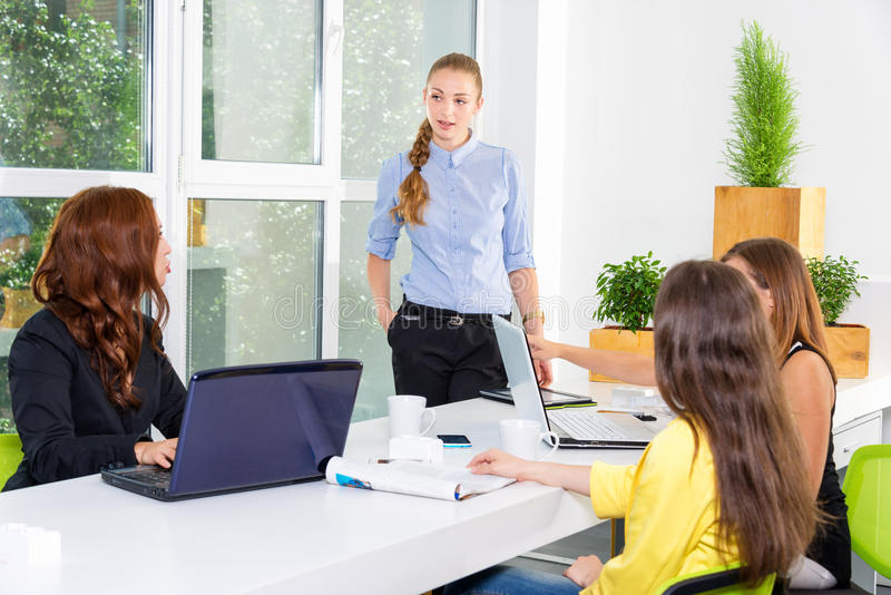 Pretty young business woman giving a presentation in conference or meeting setting. People and teamwork concept - happy stock photo