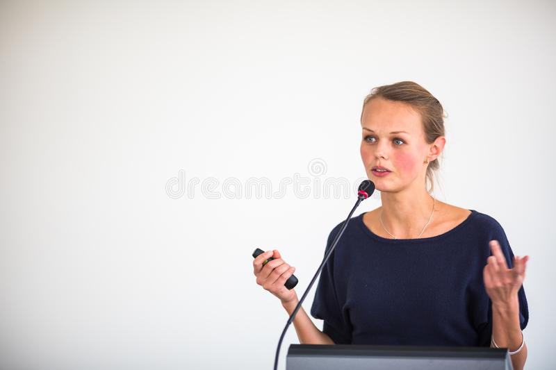 Pretty, young business woman giving a presentation in a conference/meeting setting royalty free stock image