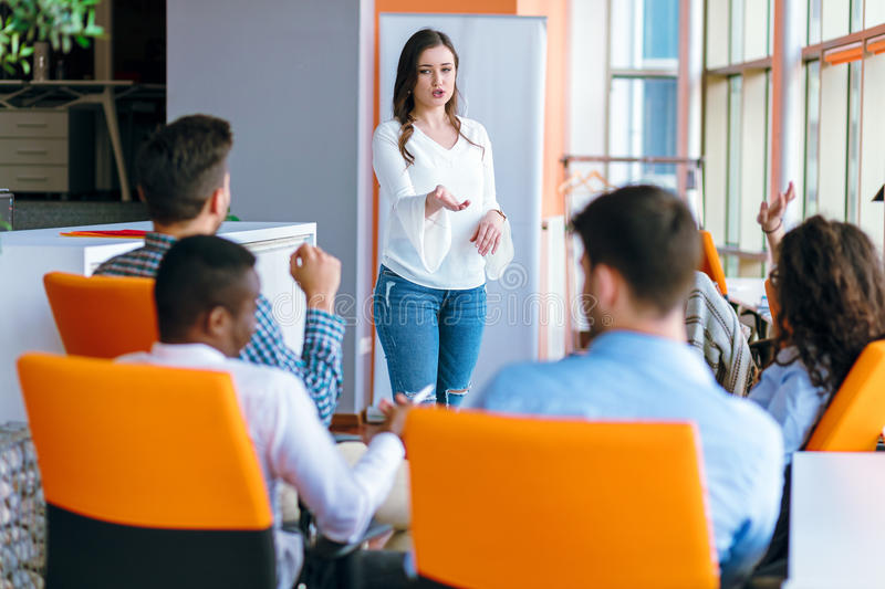 Pretty young business woman giving a presentation in conference or meeting setting. royalty free stock photos