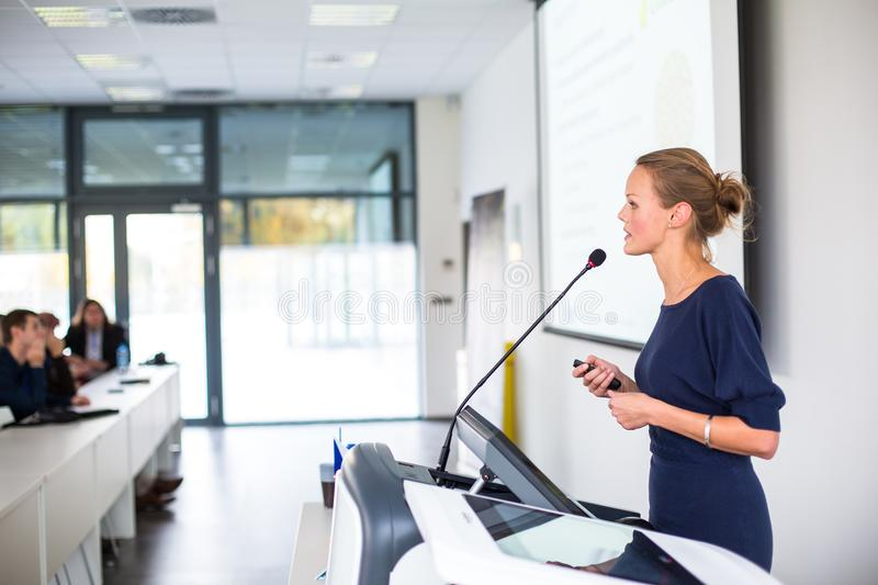 Pretty, young business woman giving a presentation in a conference royalty free stock photos