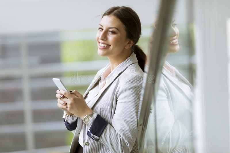 Pretty young business woman stands on the stairs at the office and use mobile phone royalty free stock photo
