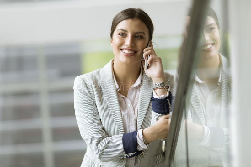 Pretty young business woman stands on the stairs at the office and use mobile phone stock photography