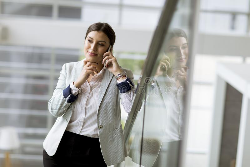 Pretty young business woman stands on the stairs at the office and use mobile phone stock photo