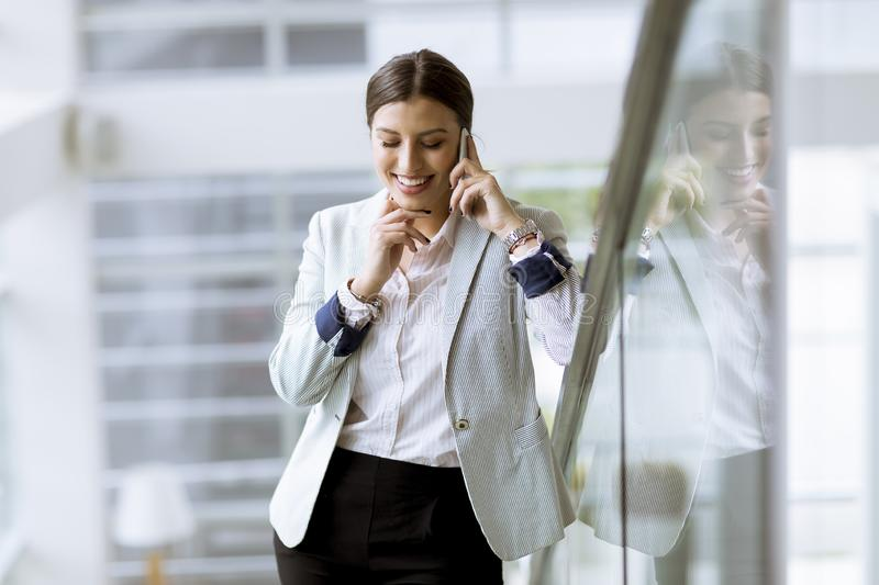 Pretty young business woman stands on the stairs at the office and use mobile phone royalty free stock photos