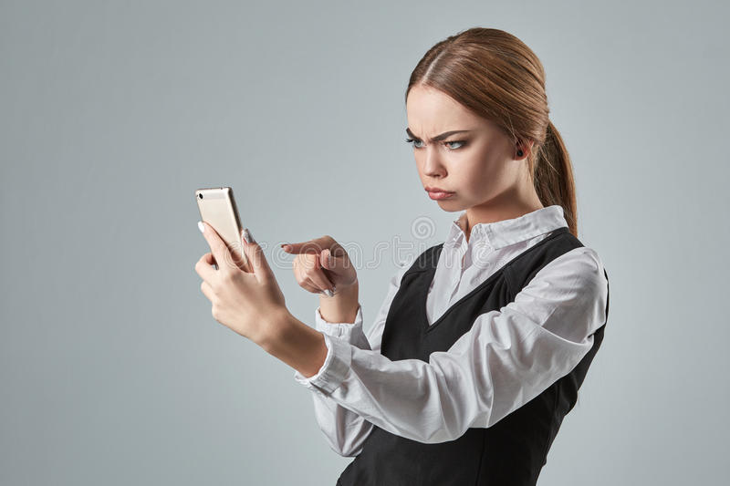 Pretty young business woman using mobile phone indoor. Gray background royalty free stock photography