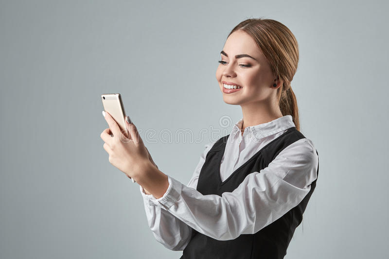 Pretty young business woman using mobile phone indoor. Gray background royalty free stock photo