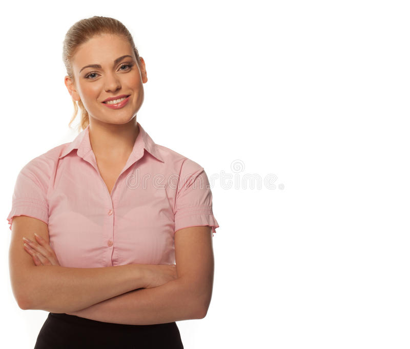 Pretty young business woman on white. Studio portrait over white of a young business woman, with arms crossed, smiling directly to the camera. Space for your royalty free stock photos