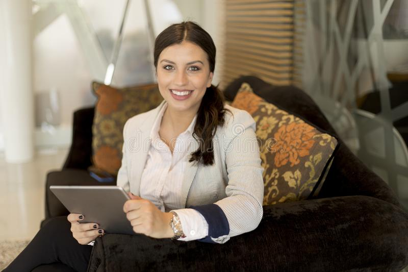 Pretty young businesswoman with digital tablet sitting in office waiting room royalty free stock photo