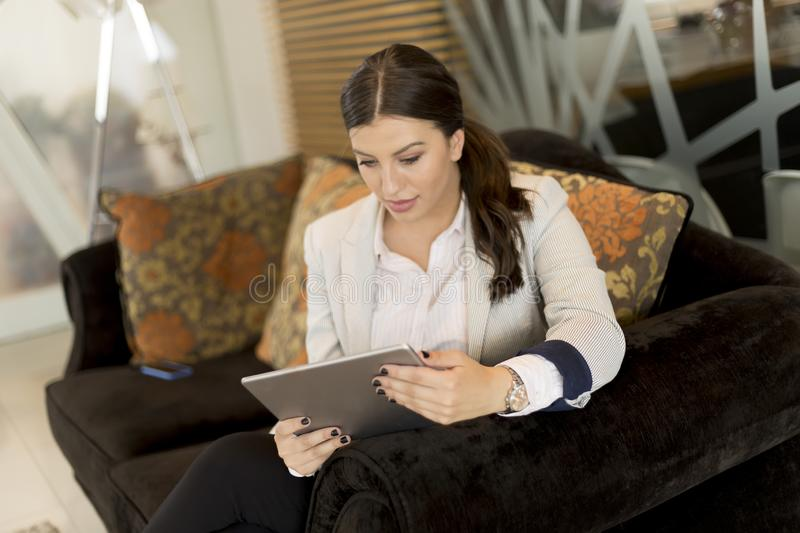 Pretty young businesswoman with digital tablet sitting in office waiting room stock photos