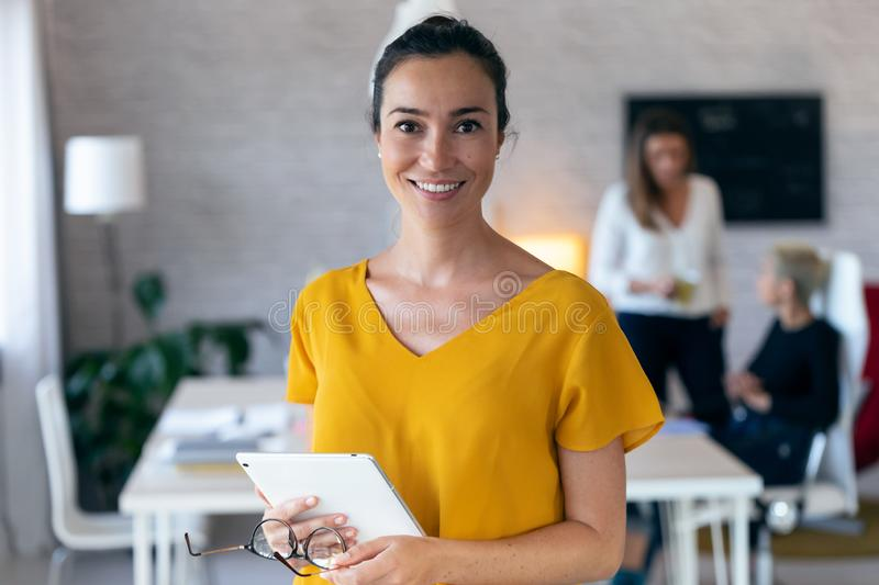 Pretty young businesswoman looking at camera. In the background, her colleagues working in the office. Portrait of pretty young businesswoman looking at camera stock images