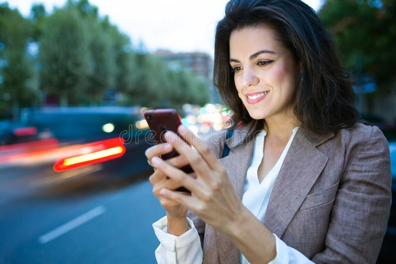 Pretty young businesswoman texting with her smartphone in the street near the highway. royalty free stock images