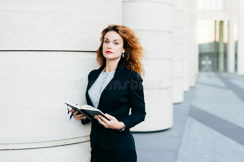 Pretty young businesswoman wearing black jacket, skirt and white blouse, holding her pocket book with pen, writing notes or lookin. G for spare days in order to stock photos