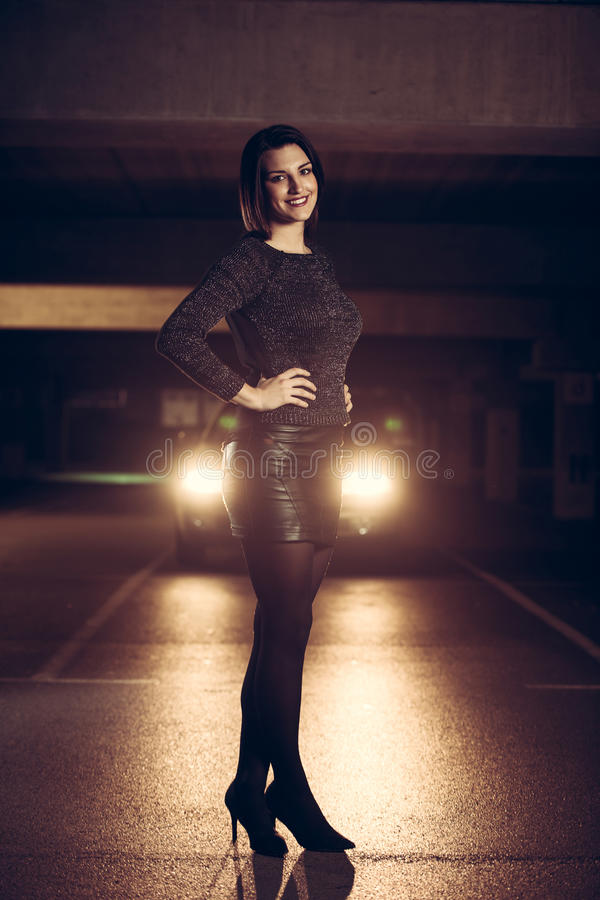 Pretty young caucasian woman with brown hair night portrait in i. Pretty young caucasian woman night portrait in industrial environment royalty free stock images