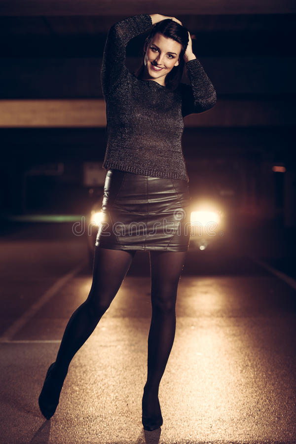 Pretty young caucasian woman with brown hair night portrait in i. Pretty young caucasian woman night portrait in industrial environment royalty free stock photography