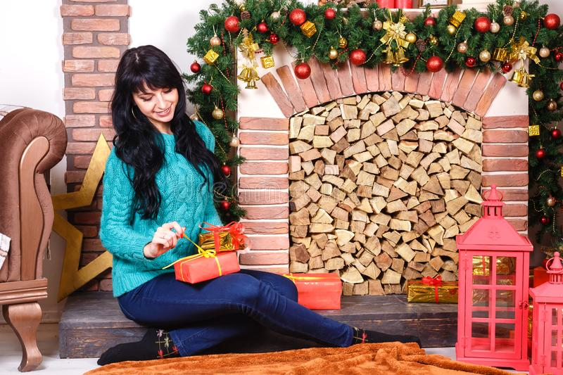 Pretty young caucasian woman sitting near a decorative fireplace royalty free stock photography