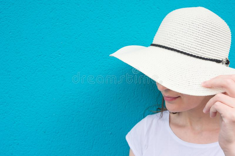 Pretty Young Caucasian Woman in Straw Sun Hat White T-Shirt on Turquoise Painted Wall Background. Urban Lifestyle stock photography