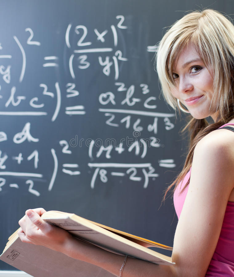Pretty young college student. Writing on the chalkboard/blackboard during a math class stock photography