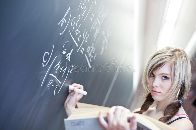 Pretty young college student. Writing on the chalkboard/blackboard during a math class royalty free stock image