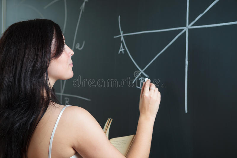 Pretty young college student drawing on the chalkboard. Pretty, young college student drawing on the chalkboard/blackboard during a math class (shallow DOF stock images