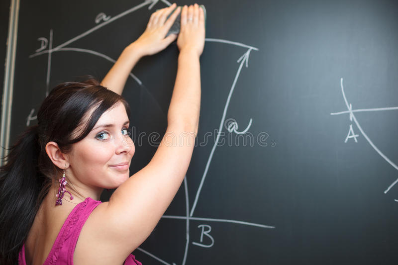 Pretty young college student drawing on the chalkboard. Pretty, young college student drawing on the chalkboard/blackboard during a math class (shallow DOF royalty free stock images