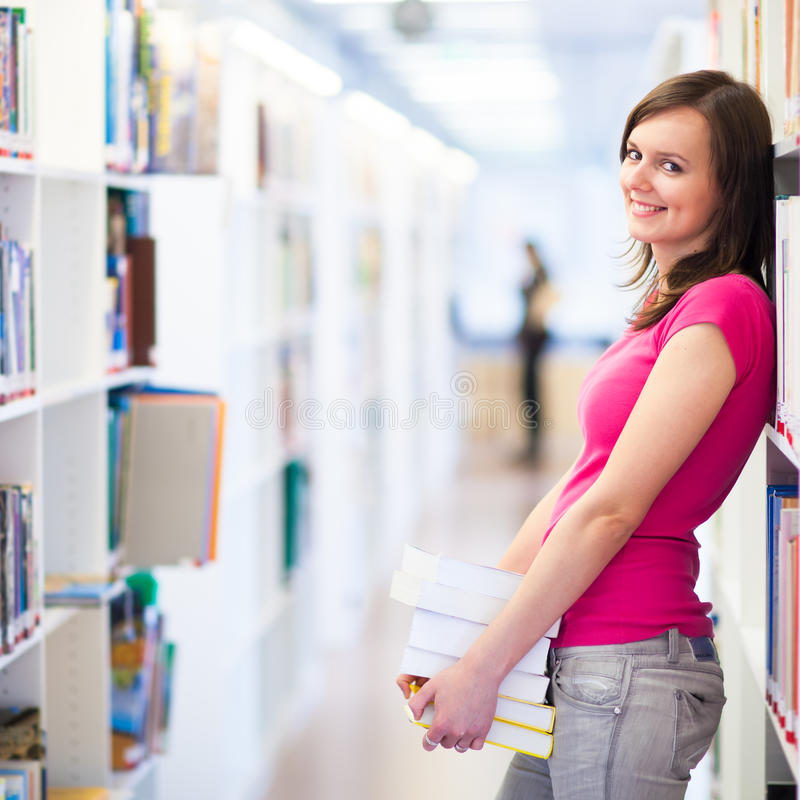 Pretty young college student in a library stock images
