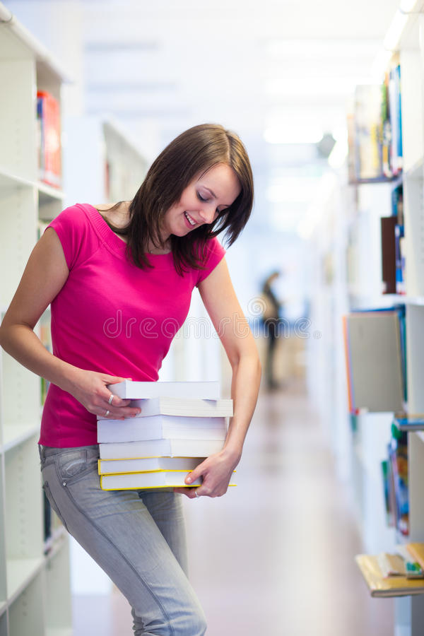 Pretty young college student in a library stock photos