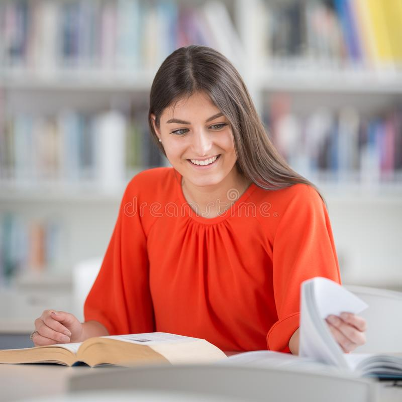 Pretty, young college student looking for a book in the library royalty free stock photography