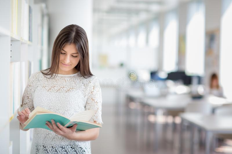 Pretty, young college student looking for a book in the library royalty free stock photos