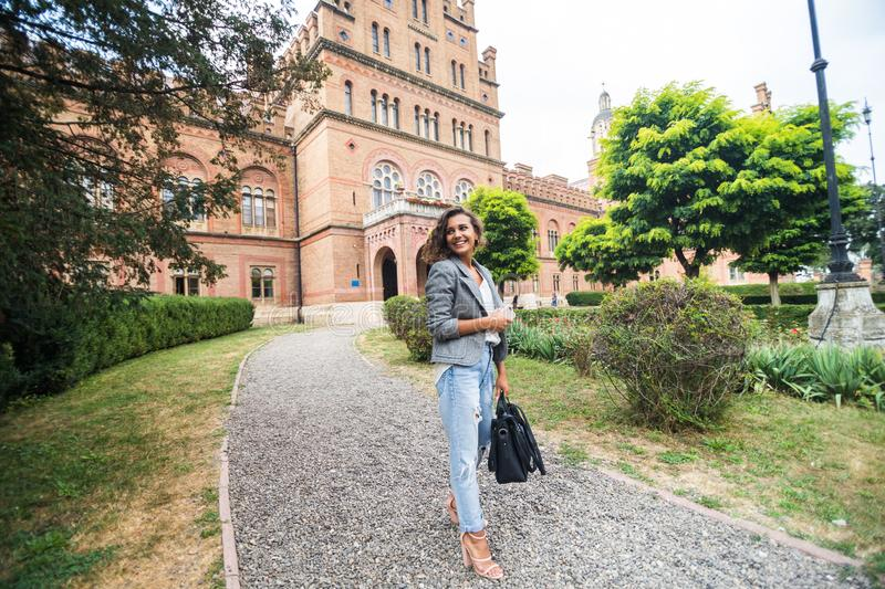 Pretty young college student smiling happy, holding a backpack are a walk to class in the University stock photos
