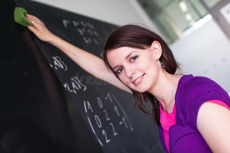 Pretty, young college student wiping the chalkboard/blackboard between classes (shallow DOF; color toned image). Pretty, young college student writing on the royalty free stock photography