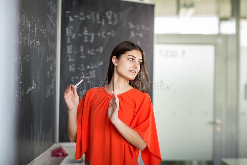 Pretty, young college student writing on the chalkboard. /blackboard during a math class royalty free stock photography