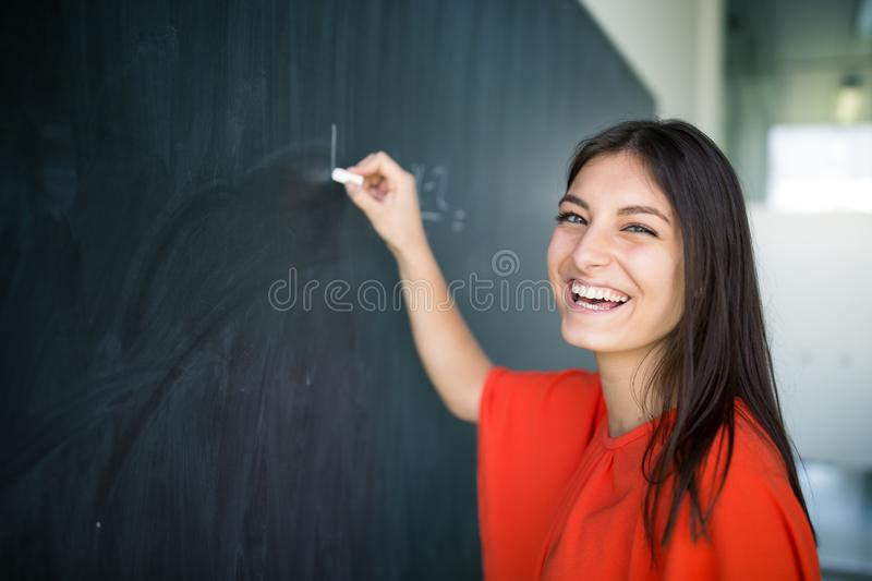 Pretty, young college student writing on the chalkboard. /blackboard during a math class royalty free stock image